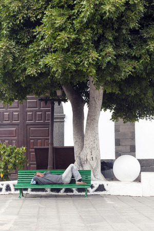 ARRECIFE, SPAIN - APRIL 3: man holds a siesta on a bench on April 3, 2012 in Arrecife, Spain. Siesta is the traditional off time from noon to 3 pm in Spain.