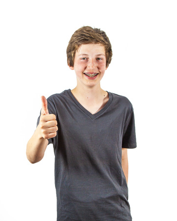 teenage boy with retainer smiles and gives thumbs up sign photo