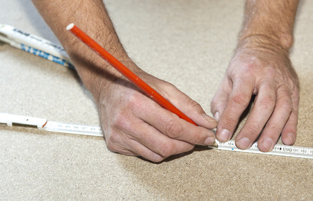 yardstick: man uses a white yardstick to mark the chip board