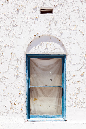old peeling white wall with window in detail photo
