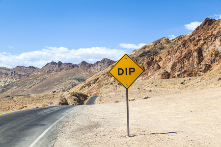 vastness: scenic road Artists Drive in Death valley with road sign DIP for hilly road under blue sky Stock Photo