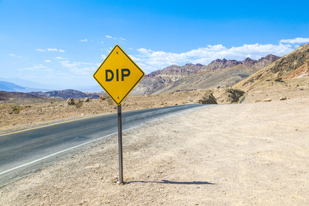 scenic road Artists Drive in Death valley with road sign DIP for hilly road under blue sky photo