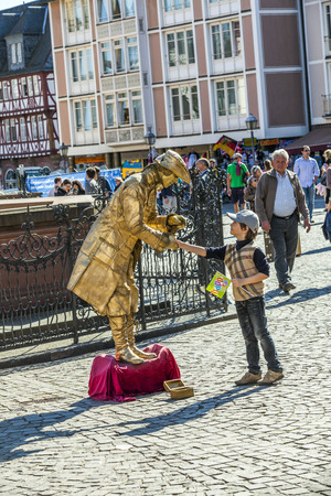 roemer: FRANKFURT, GERMANY - MARCH 25: pantomime in golden ancient dress greets a boy on March 25, 2012 in Frankfurt, Germany. Street performers need in Frankfurt a licence to do their job.