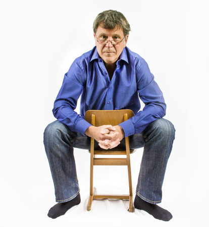 handsome man sits on a small wooden chair and poses Stock Photo