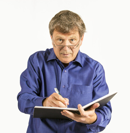 business man in blue shirt writes in his diary photo