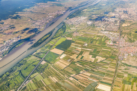 hesse: aerial of small village with fields in afternoon light at river rhine