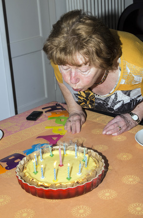 inference: A senior female blows out candles on a cake. Ideal for birthday, anniversary or any other celebration inference. Stock Photo