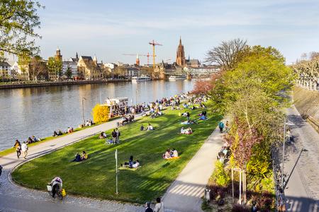 sachsenhausen: Francoforte, Germania - 29 marzo: le persone godono il primo giorno di primavera caldo su 29 marzo 2014 a Francoforte, in Germania. Si rilassano al fiume principale con vista Skyline di Francoforte.