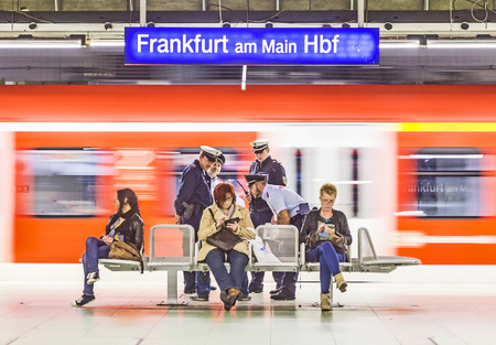 valid: FRANKFURT, GERMANY - MARCH 29: railway police checks a passenger for a valid ticket on March 29, 2014 in Frankfurt, Germany. Travel without valid ticket is charged with 50 EUR fine.
