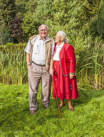 elderly couple sitting hand in hand in their garden photo