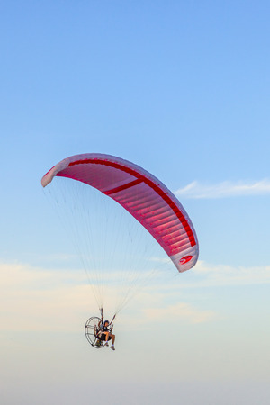 regulated: MIAMI, USA - JULY 26: Paraglider flying along the beach on July 26, 2010 in Miami, USA. In the USA powered paragliding is minimally regulated and requires no licence.