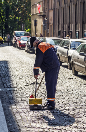 tender's: KRAKOW, POLAND - MAY 5: government man cleans the street on May 5, 2013 in Krakow, Poland. Street cleaning is offered by public tenders to private companies.
