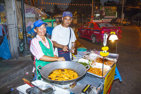 BANGKOK, THAILAND - DEC 23, 2009: An unidentified chef cooks food at a street-side restaurant in Bangkok, Thailand. There are 16,000 registered street vendors in Bangkok according to government stats.