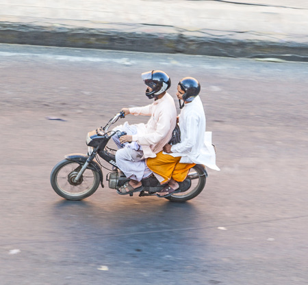 JAIPUR, INDIA - NOV 13, 2011: Two men riding on a bike (blurred motion). Motorbike is the most favorite vehicle and most affordable for India.