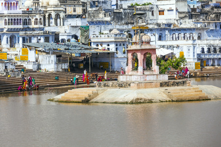 PUSHKAR, INDIA - OCTOBER 20, 2012: Pilgrims take ritual bathing in holy lake in Pushkar, Rajasthan, India. It is one of the five sacred pilgrimage site for devout Hindus.