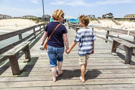 nags: madre e hijo caminando de la mano en el famoso muelle en Nags Head