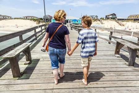 nags: mother and son walking hand in hand at famous pier in Nags Head
