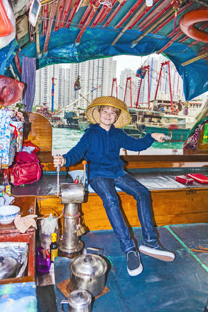 tourists on a boat cruise with traditional wooden junk in Aberdeen, Hongkongs