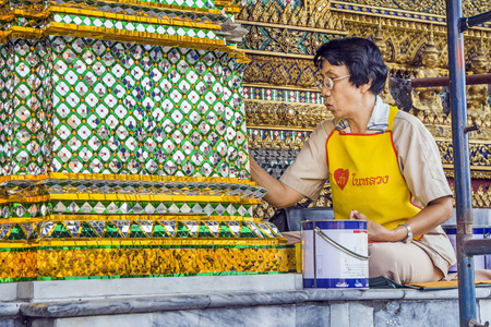 restoring: BANGKOK, THAILAND - DECEMBER 26, 2007: woman is restoring a mosaique at the wall in the grand palace in Bangkok, Thailand. There are permanently working more than 300 people for keeping the temple in good condition. Editorial