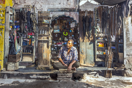 JODPUR, INDIA - OCTOBER 23, 2012: indian man sells household goods on a street shop in Jodhpur, India. Jodhpur is the second largest city in the Indian state of Rajasthan with over 1 million habitants.