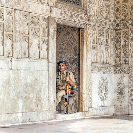 DELHI, INDIA - NOVEMBER 9, 2011  policeman pays attention in the Red Fort to protects visitors from crime  in Delhi, India  Red Fort is a 17th century fort complex was designated a UNESCO World Heritage Site in 2007
