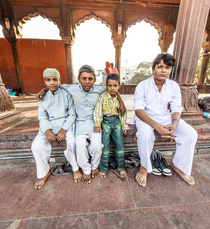 DELHI, INDIA - NOVEMBER 8, 2011: A group of worshipers rest on the courtyard of Jama Masjid Mosque in Delhi, India. Jama Masjid is the principal mosque of Old Delhi in India.
