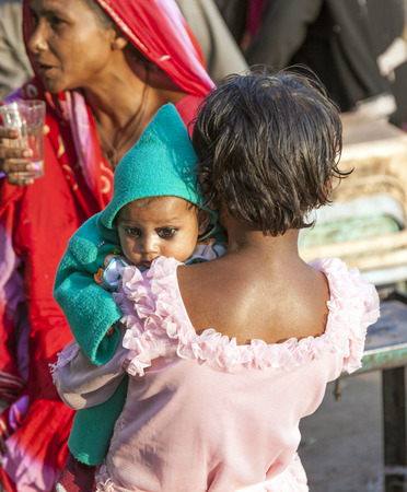 DELHI - NOV 8, 2011: young girl holds her baby sister in the arm  at the Meena Bazaar Market in Delhi, India. Shah Jahan founded the bazaar in the 17th century inspired by the architecture of the Isfahan Bazaar.