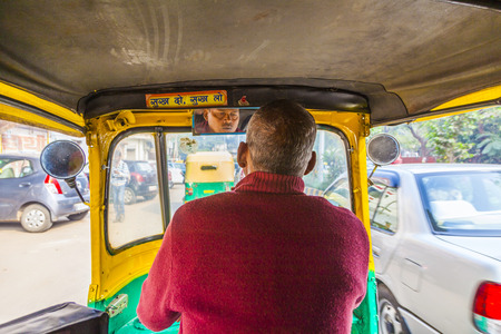 DELHI, INDIA - NOV 11, 2011: Auto rickshaw taxi driver in Delhi, India. These iconic taxis have recently been fitted with CNG powered engines in an effort to reduce pollution.