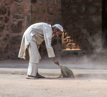 DELHI, INDIA - NOV 11, 2011: workers at Humayun's Tomb cleans the yard in Delhi, India. They also get alms by religious people. The tomb was built by Hamida Banu Begun in 1565-72 A.D.. Stock Photo - 28946432
