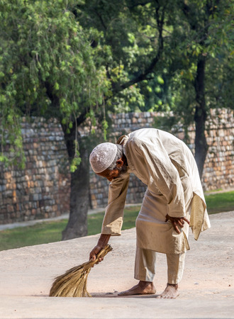 DELHI, INDIA - NOV 11, 2011: workers at Humayun's Tomb cleans the yard in Delhi, India. They also get alms by religious people. The tomb was built by Hamida Banu Begun in 1565-72 A.D.. Stock Photo - 28946434