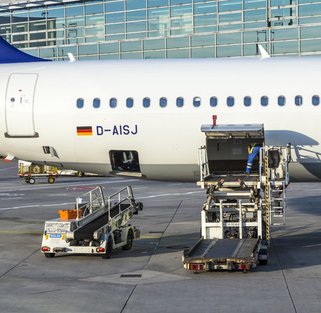 FRANKFURT, GERMANY - JUNE 13, 2014: people load Lufthansa Aircrafts  with freight at the terminal 1 at Frankfurt airport. Frankfurt is one of the busiest airport in Europe and Number one in Germany.