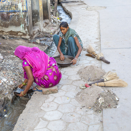 BIKANER, INDIA - OCT 24, 2012: woman tries to find gold dust in the canalisation of the gold smith area in Bikaner, India.