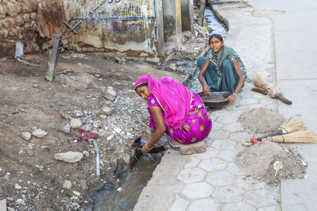 bikaner: BIKANER, INDIA - OCT 24, 2012: woman tries to find gold dust in the canalisation of the gold smith area in Bikaner, India.
