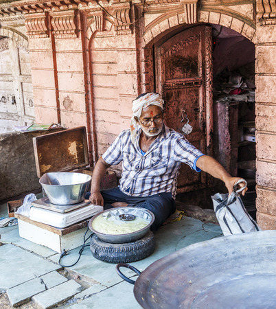 BIKANER, INDIA - OCT 24, 2012: man sells delicious curd in the streets of Bikaner, India. Curds are a dairy product obtained by curdling milk with rennet or any edible acidic substanc.