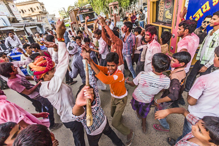 celebrated: MANDAWA, INDIA - OCT 24, 2012: People throw colors, mostly red, to each other during the Holi celebration in Mandawa, India. Holi is the most celebrated religious color festival in India.