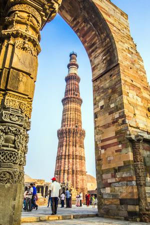 minar: DELHI, INDIA - MARCH 27, 2012: Unidentified tourists walk around Qutub Minar complex in Delhi, India. Qutub Minar is the tallest minar in India, originally an ancient Islamic Monument.