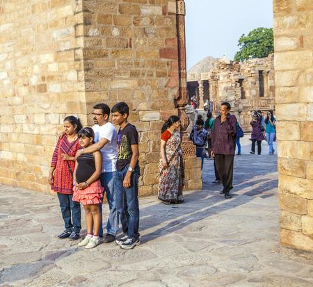 DELHI, INDIA - MARCH 27, 2012: Unidentified tourists walk around Qutub Minar complex in Delhi, India. Qutub Minar is the tallest minar in India, originally an ancient Islamic Monument.
