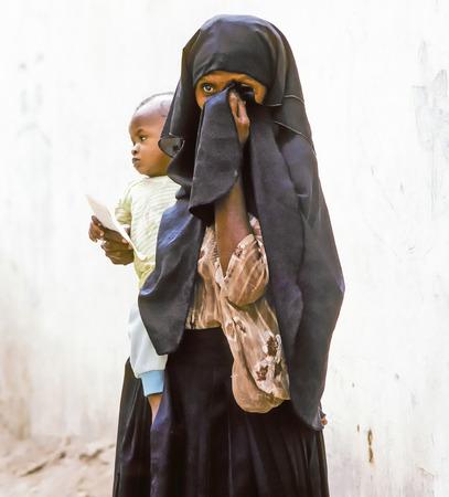 illiteracy: Hadhramaut, YEMEN - MAY 15: madre desconocida �rabe lleva a su beb� en un vestido envolvente el 15 de mayo de 1993 en Hadramaut, Yemen. en 2008 todav�a el 62 por ciento de las mujeres de las zonas rurales son el analfabetismo.