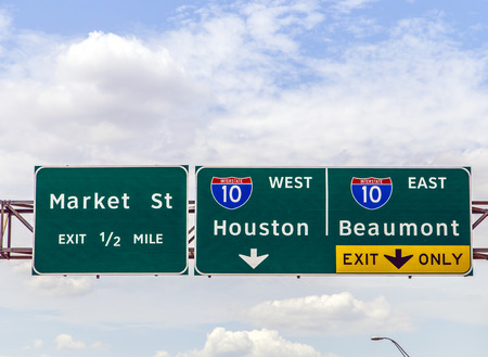 highway signs: street signs at the interstate in Texas under blue sky