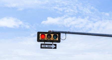 leaning on the truck: red traffic light with one way sign under blue sky