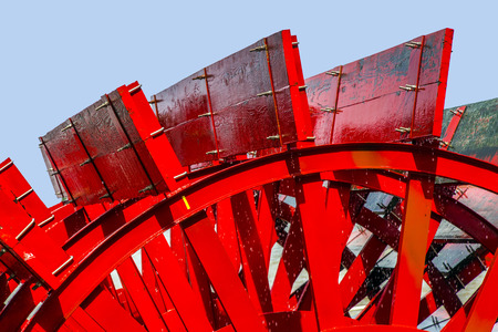 paddle wheel: Red Riverboat Paddle Wheel in a River with Trees Stock Photo
