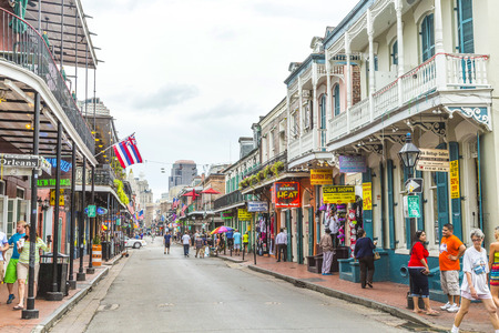 bourbon street: NEW ORLEANS, LOUISIANA USA - JULY 16, 2013: people visit historic building in the French Quarter  in New Orleans, USA. Tourism provides a large source of revenue after the 2005 devastation of Hurricane Katrina.