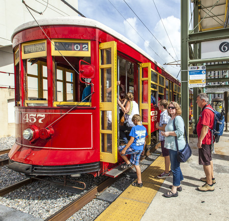 NEW ORLEANS, LOUISIANA-JULY 16, 2013: people enter  the riverfront  Streetcar Line in New Orleans, USA. Revamped after Hurricane Katrina in 2005, the New Orleans Streetcar line began electric operation in 1893.
