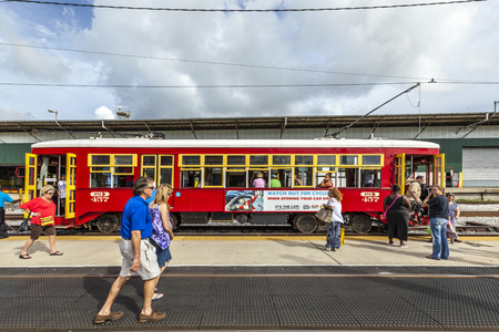 streetcar: NEW ORLEANS, USA - JULY 16, 2013: people enter  the riverfront  Streetcar Line in New Orleans, USA. Revamped after Hurricane Katrina in 2005, the New Orleans Streetcar line began electric operation in 1893.