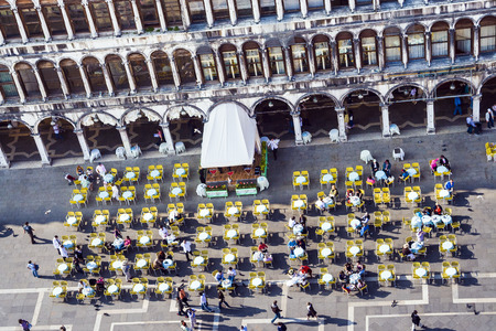 VENICE, ITALY - APRIL 11, 2007: people enjoy sitting at famous marcus place with cafe and tables in Venice, Italy.