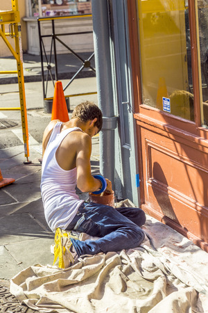 bourbon street: NEW ORLEANS, USA - JULY 17, 2013:  man paints wooden window of  historic building in New Orleans, USA. Tourism provides a large source of revenue after the 2005 devastation of Hurricane Katrina.