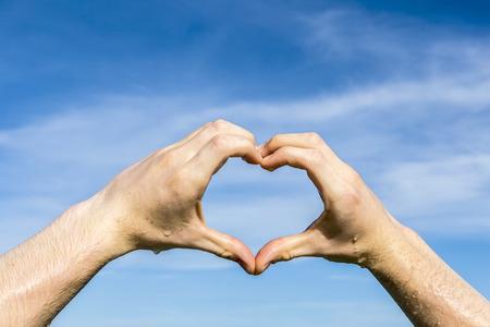 heart shape with hand under blue sky in sun photo