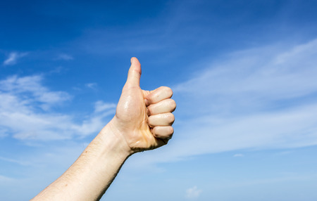 arms up: thumbs up sign under blue sky Stock Photo