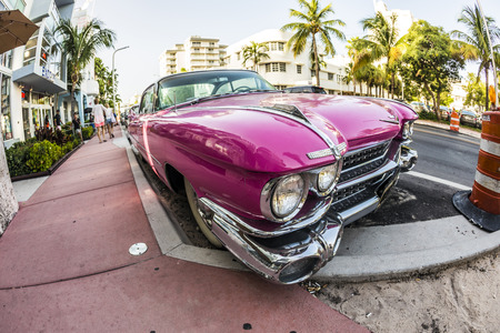 artdeco: MIAMI, USA - AUG 18, 2014 : Cadillac Vintage car parked at Ocean Drive in Miami Beach, Florida. Art Deco architecture in South Beach is one of the main tourist attractions in Miami