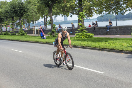 COLOGNE, GERMANY- SEP 7, 2014: An athlete cycles in the Cologne Triathlon in Cologne, Germany. The event takes place first in 1984 and is performed ince then yearly in the City area of Cologne. Editöryel